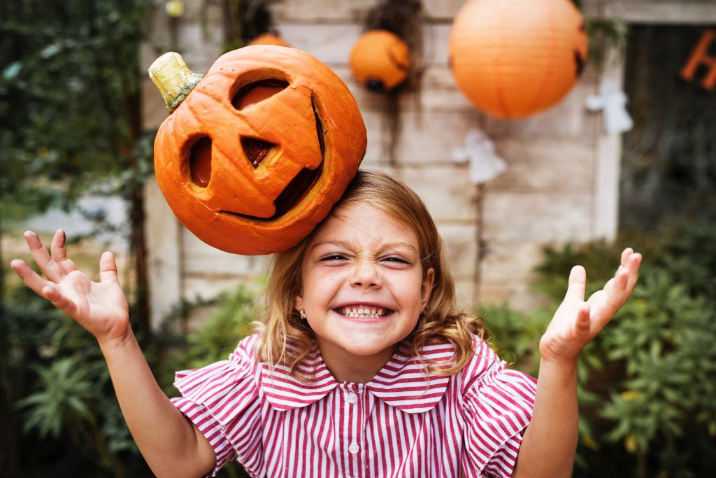 little girl smiling with a pumpkin on her head