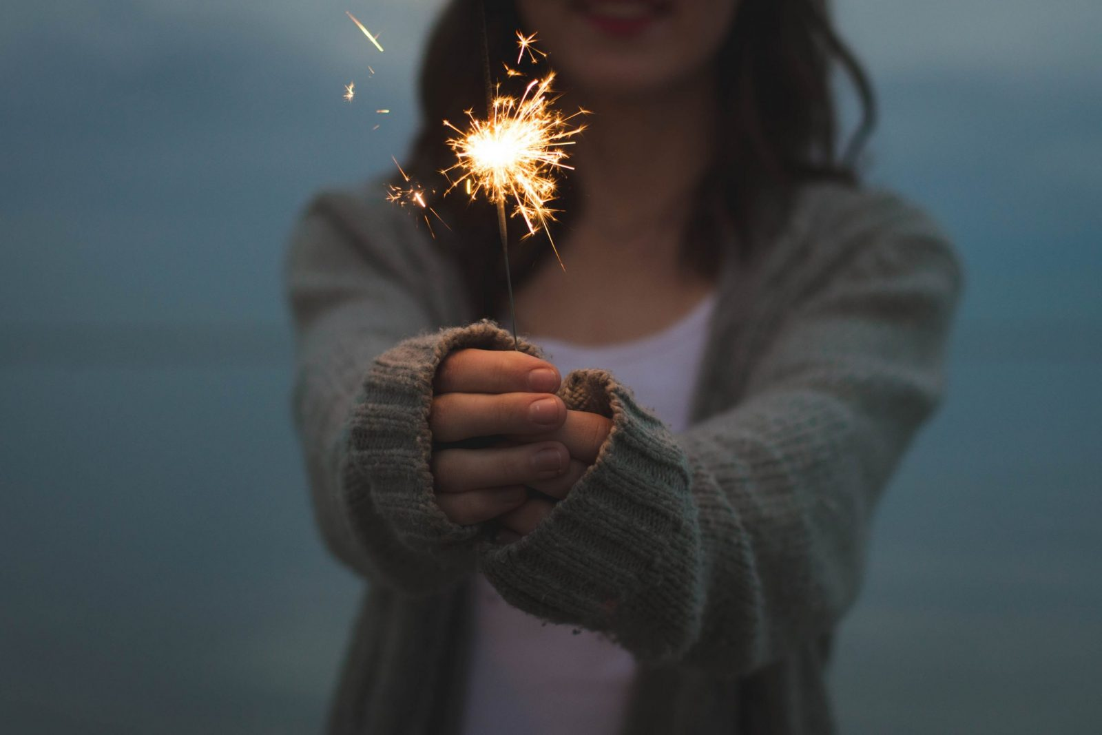 a girl holding a sparkler cozy winter