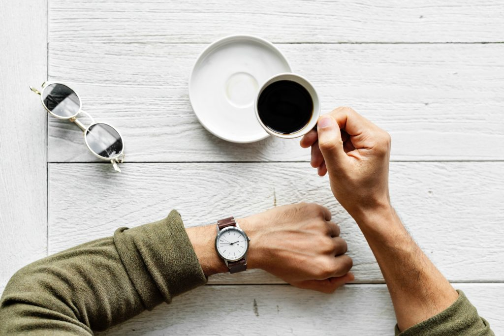 a person holding a cup of coffee looks at one's watch