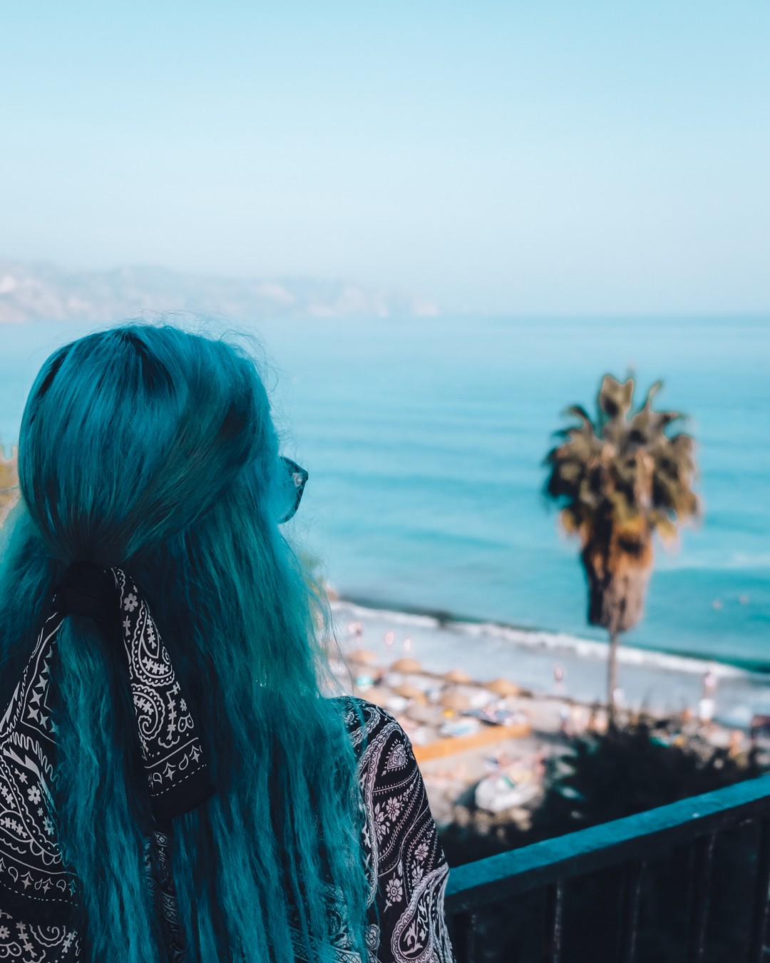 Stylish blue-haired girl looking at sea, a palm nearby and a beautiful seashore with sky-blue water.