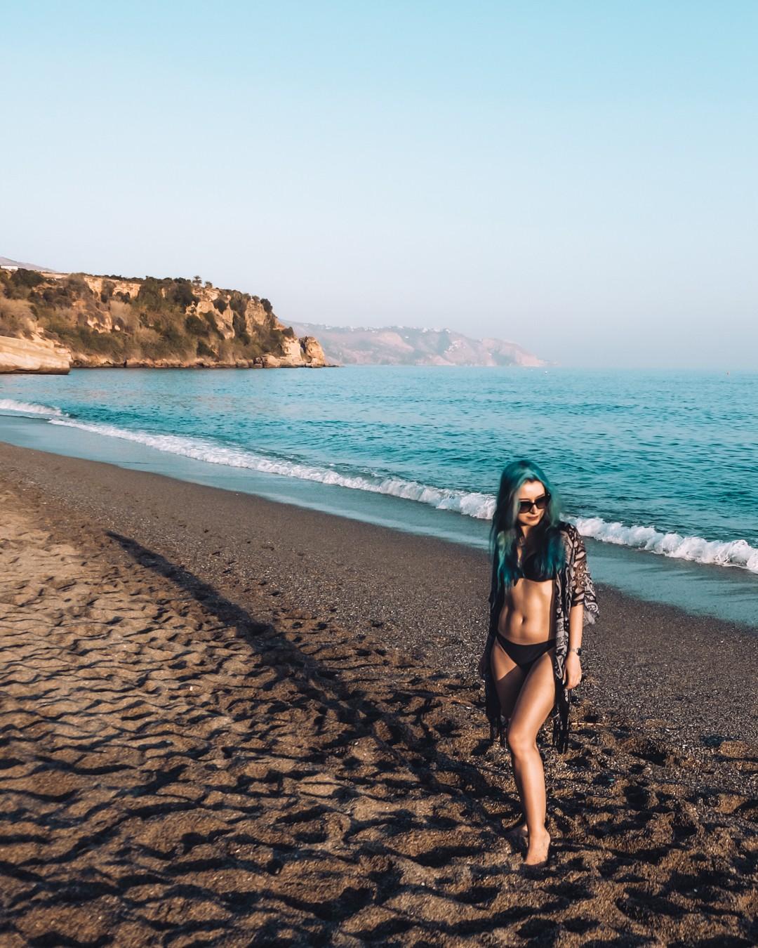 A girl with blue hair in bikini posing on the beautiful empty beach.
