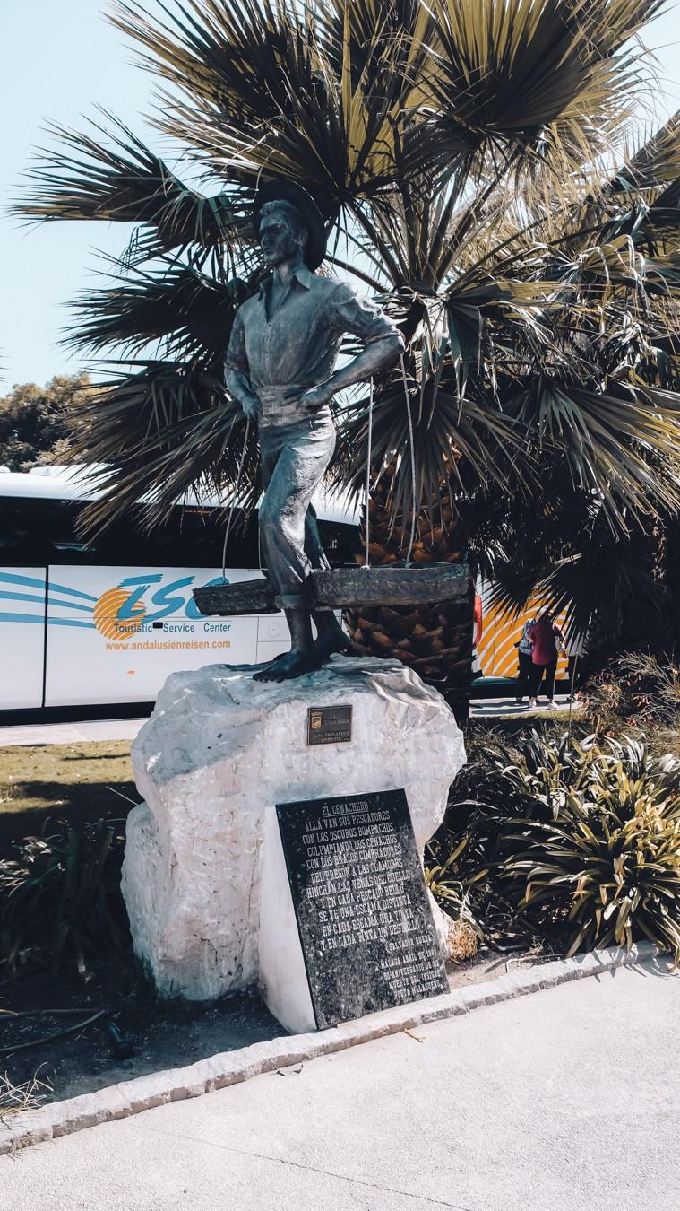 Statue of fisherman in the Malaga botanical garden.