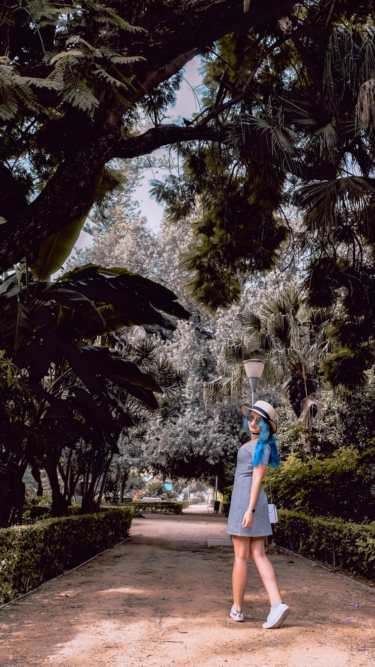 Blu haired girl in botanical garden Parque de Malaga.