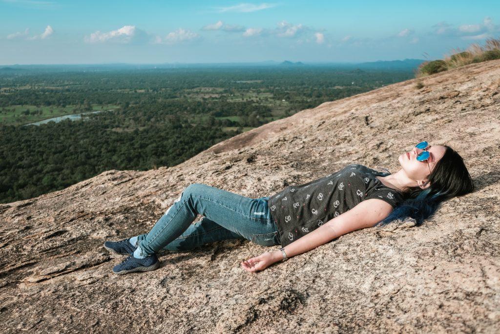 girl laying on top of pidurangala rock sigiriya