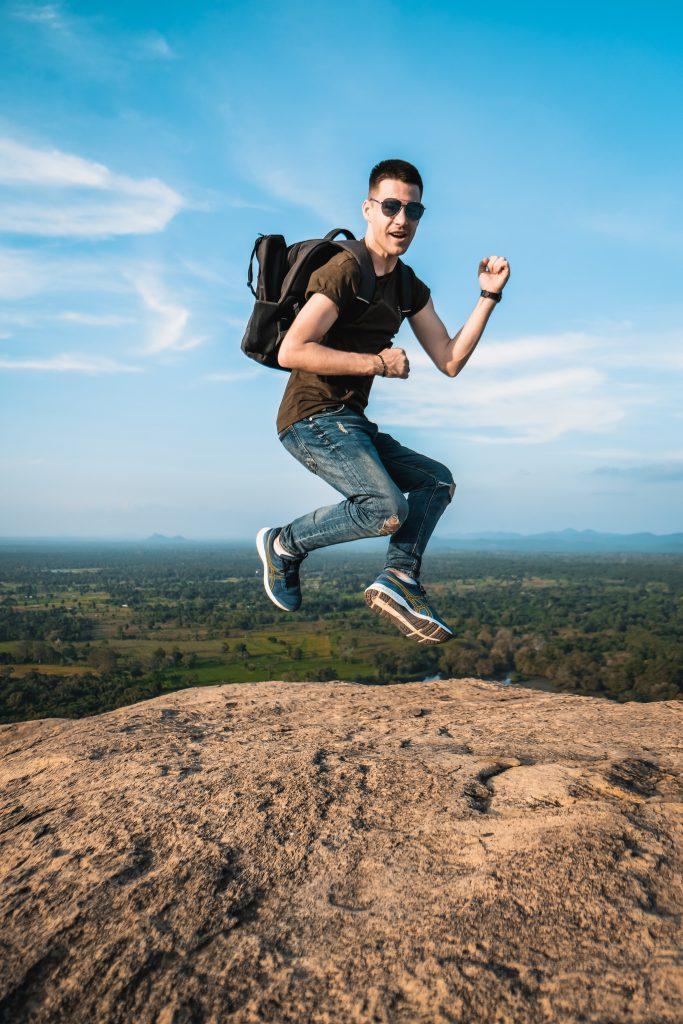 young men jumping at the top of pidurangala rock
