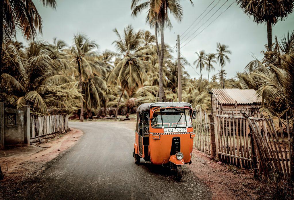 orange tuk tuk on the road sri lanka