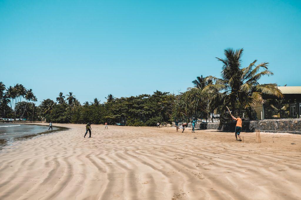 locals playing cricket on sri lanka beach
